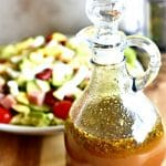 Balsamic Vinaigrette Salad Dressing in a bottle with a salad and salt and pepper grinder in the background