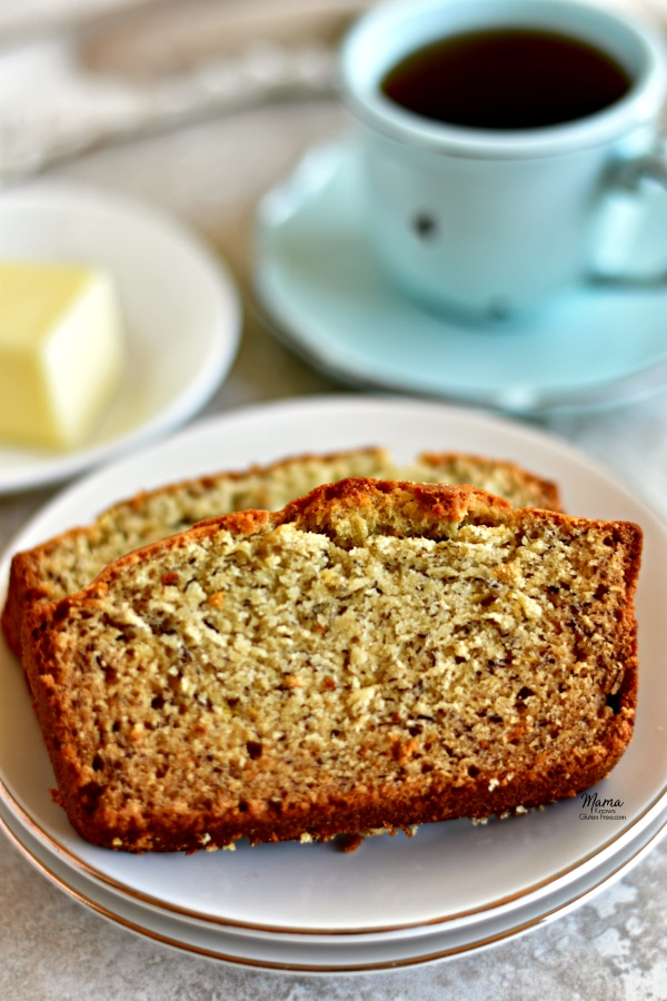 2 slices of gluten-free banana bread on a plate with coffee cup and butter in the background