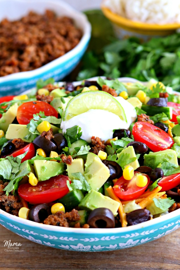 gluten-free burrito bowl with taco meat, rice and cilantro int he background