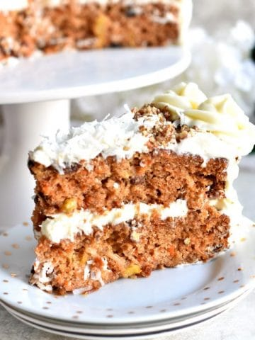 a slice of gluten-free carrot cake with cream cheese frosting and the cake on a cake stand in the background