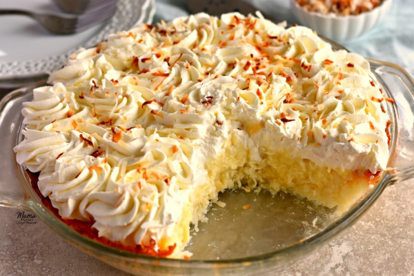 A Gluten-Free Coconut Cream Pie with a slice cut out of it.