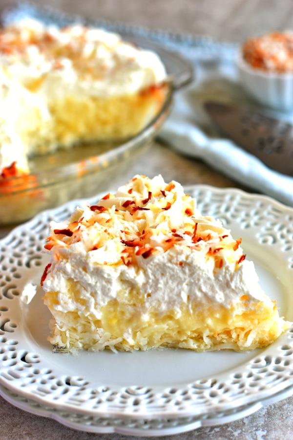 A slice of gluten-free coconut cream pie on a plate with the pie and toasted coconut in the backgorund