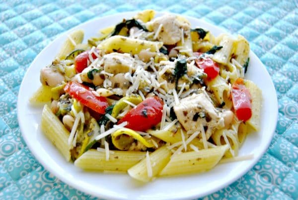 gluten-free penne pasta with sauteed chicken and vegetables in a pesto sauce