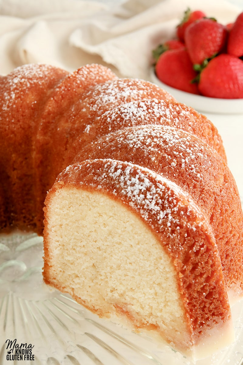 gluten-free pound cake topped with powdered sugar with strawberries in the background