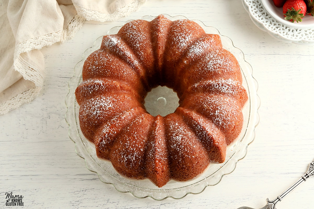 gluten-free pound cake topped with powderd sugar on a cake plate with strawberries in the background