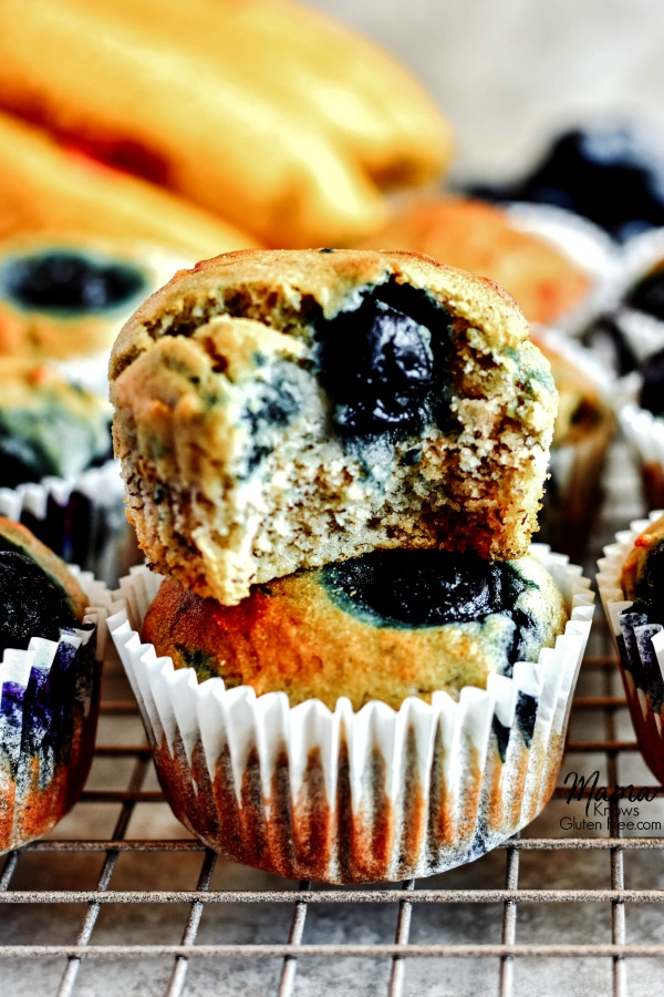2 Gluten-Free Blueberry Banana Muffins stacked on top of each other with a bite out of one with more muffins and bananas in the background