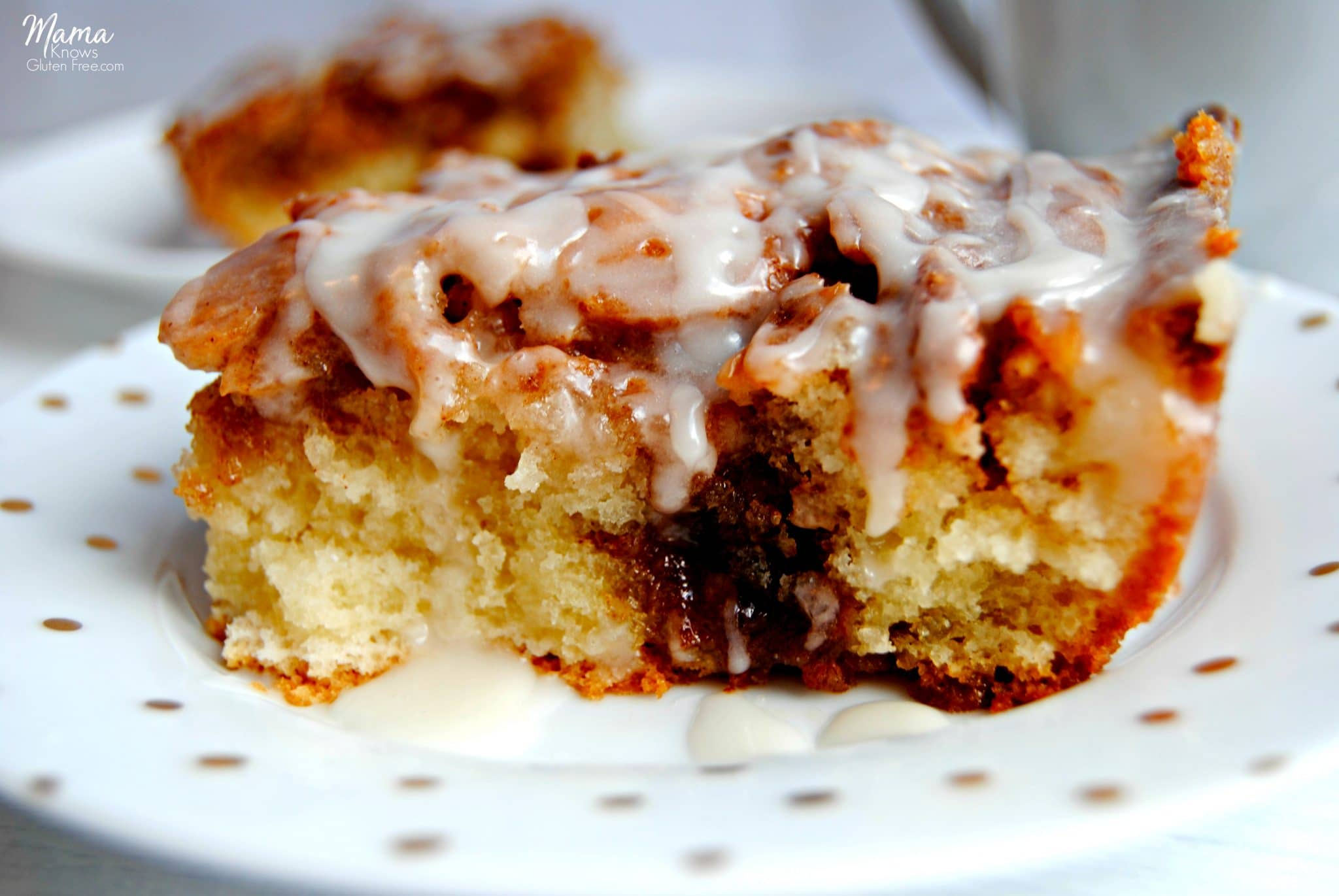 two slices of gluten-Free cinnamon roll cake on white plates with a white coffee cup.
