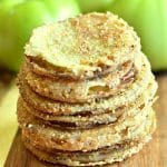a stack of gluten-free fried green tomatoes with green tomatoes in the background