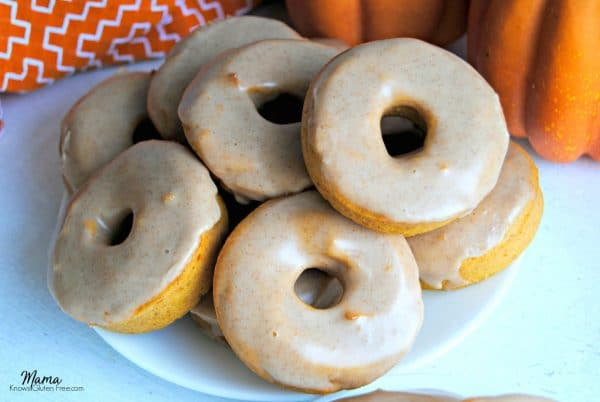 Gluten-Free Pumpkin Donuts on a white plate with pumpkins in the background