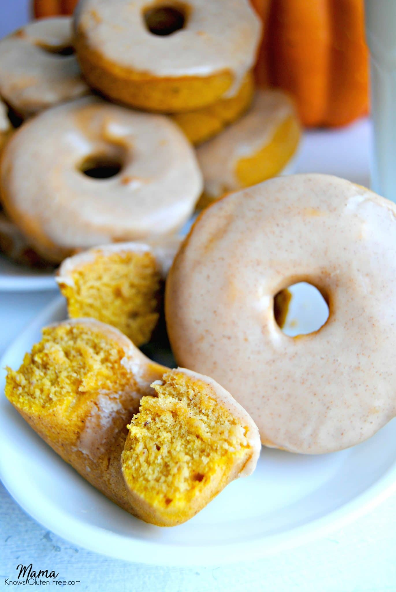 Gluten-Free Baked Pumpkin Donuts on a white plate with pumpkin is the background