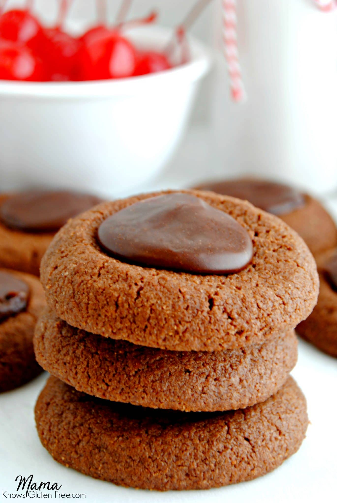 Gluten-Free Chocolate Cherry Thumbprint Cookies stacked on top of each other with cherries in the background