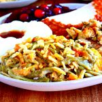 Gluten-free green bean casserole on a white plate with Thanksgiving dinner fixings.