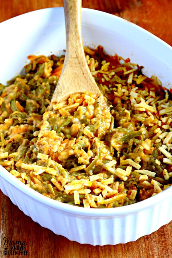 gluten-free green bean casserole in a casserole dish with a wooden spoon