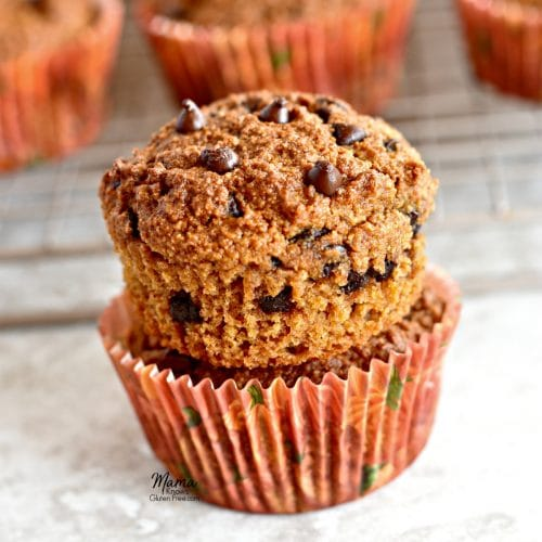 paleo pumpkin muffins stacked on top of each other with the muffins in the background