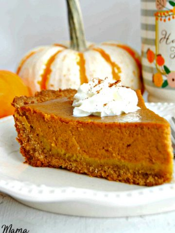 A slice of Easy Gluten-Free Pumpkin Pie with whipped cream of top with pumpkins and coffee cup in the background