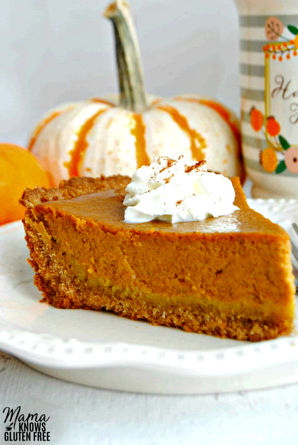 slice of gluten-free pumpkin pie topped with whipped cream with 2 pumpkins and a coffee cup in the background