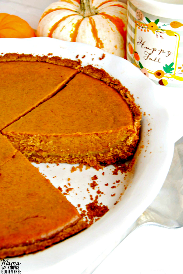 easy gluten-free pumpkin pie with a slice out of it with pumpkins and a cup in the background