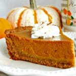 a slice of gluten-free pumpkin pie topped with whipped cream with pumpkins and a coffee cup in the background