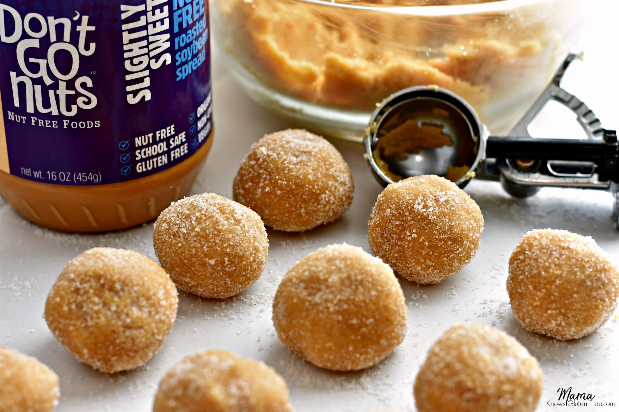 Gluten-Free Soy Butter Thumbprint Cookies balls, cookie scoop, cookie batter in a bowl and a jar of Don't Go Nuts soy butter.