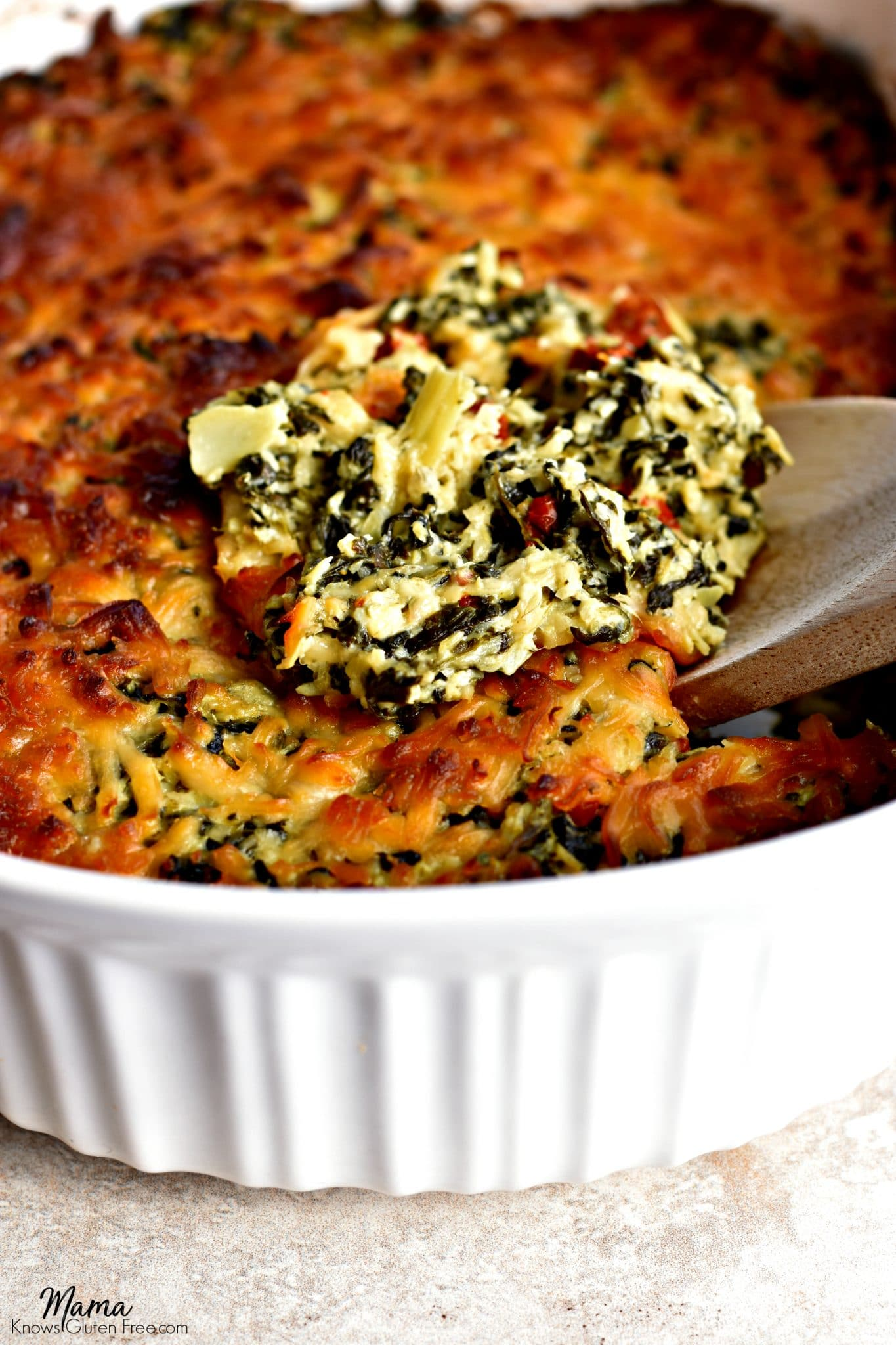 Gluten-Free Hot Spinach Artichoke Sun-Dried Tomato Dip in a casserole dish with a wooden spoon dishing out a serving.