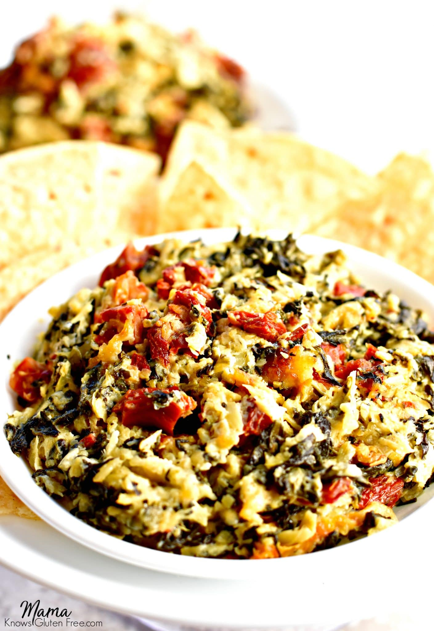 bowl of gluten-free spinach and artichoke dip with corn chips and another serving in the background.