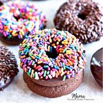 2 gluten-free chocolate donuts stacked on top of each other with 4 donuts in the background