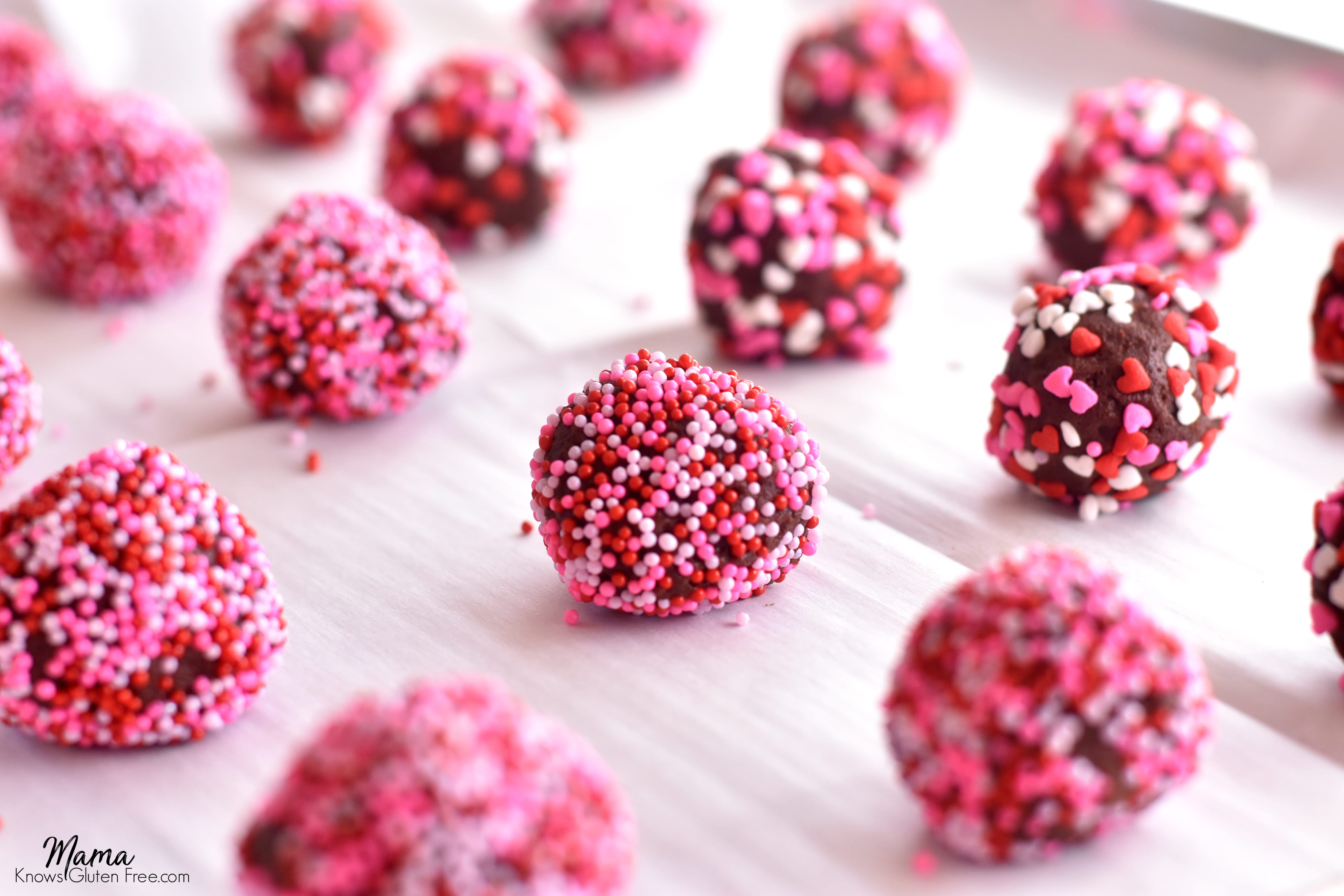 gluten-free chocolate kiss cookie balls covered in sprinkles on a cookie sheet