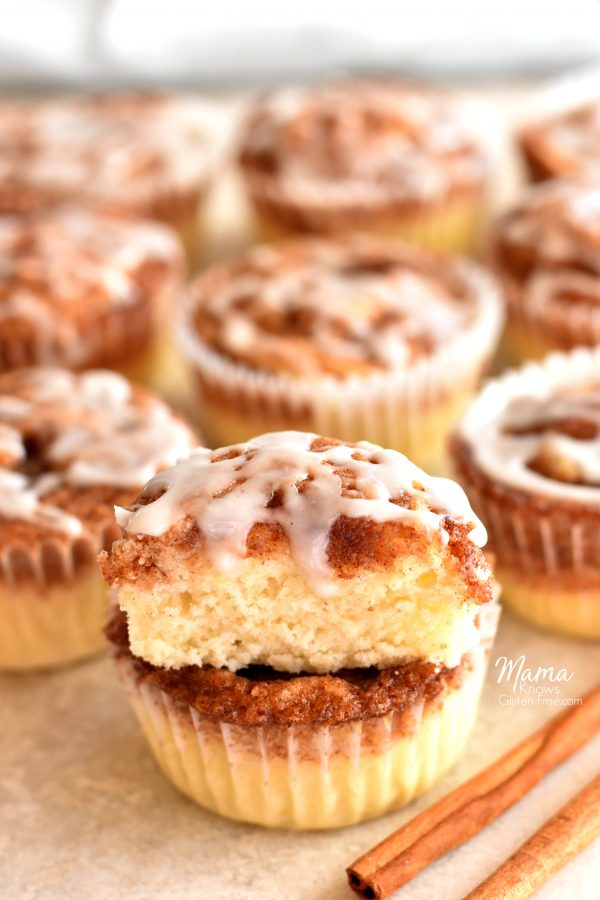 cinnamon roll muffin cut in half to show the texture with cinnamon roll muffins and cinnamon sticks