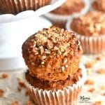 two Paleo carrot cake muffins stacked on top of each other with more muffins in the background