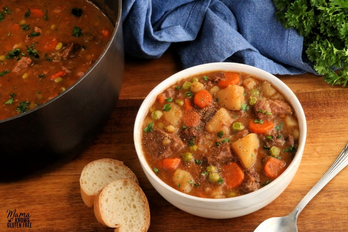 gluten-free beef stew in a white bowl with bread, a spoon and the pot in the background