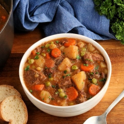 gluten-free beef stew in a white bowl with a spoon, sliced bread, pot, blue napkin, and parsley in the background