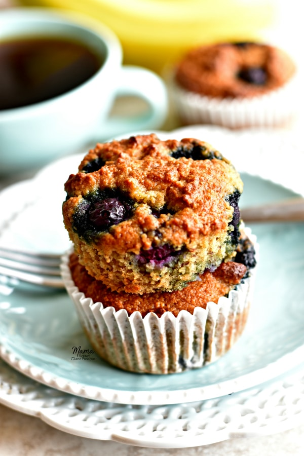 2 Paleo banana blueberry muffins stacked on top of each other on a plate with a fork, coffee cup, muffin and bananas in the background
