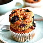 two Paleo blueberry banana muffins stacked on top of each other on a plate with a fork