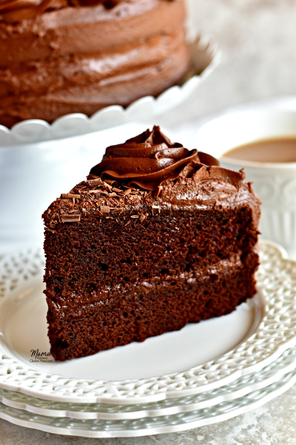 gluten-free chocolate cake slice on a white plate with the cake on a cake stand and a cup of coffee in the background