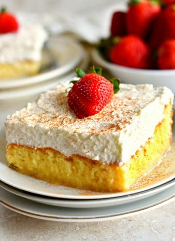 a piece of gluten-free tres leche cake on a plate with more cake and strawberries in the background