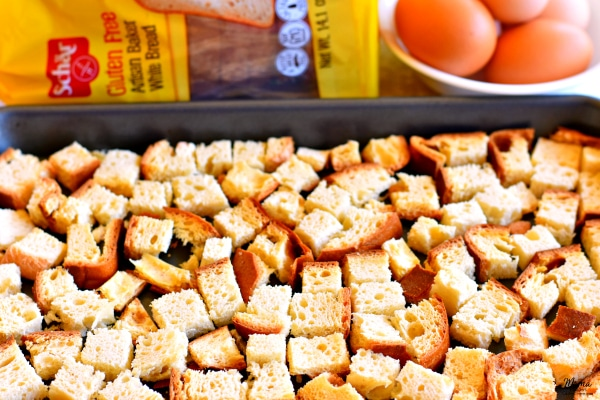Schar gluten-free bread cut into cubes on a baking sheet with bread and eggs in the background