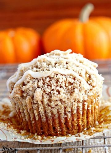 gluten-free pumpkin crumb muffin muffin on a cooling rack with pumpkins in the background