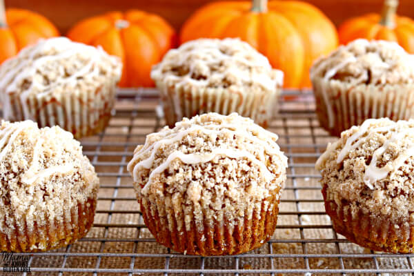 Six pumpkin crumb muffins on a cooking rack with pumpkins in the backgrounds