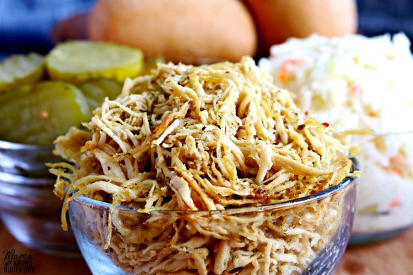 rotisserie style shredded chicken in a bowl, pickles in a bowl, coleslaw in a bowl and rolls