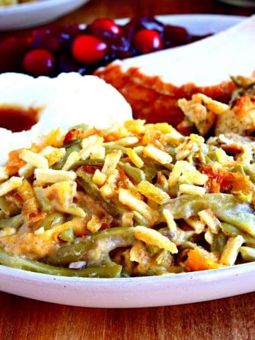 gluten-free cheesy green bean casserole ona plate with turkey, mashed potatoes, cranberry sauce.
