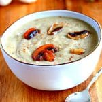 gluten-free cream of mushroom soup in a white bowl with a sppon