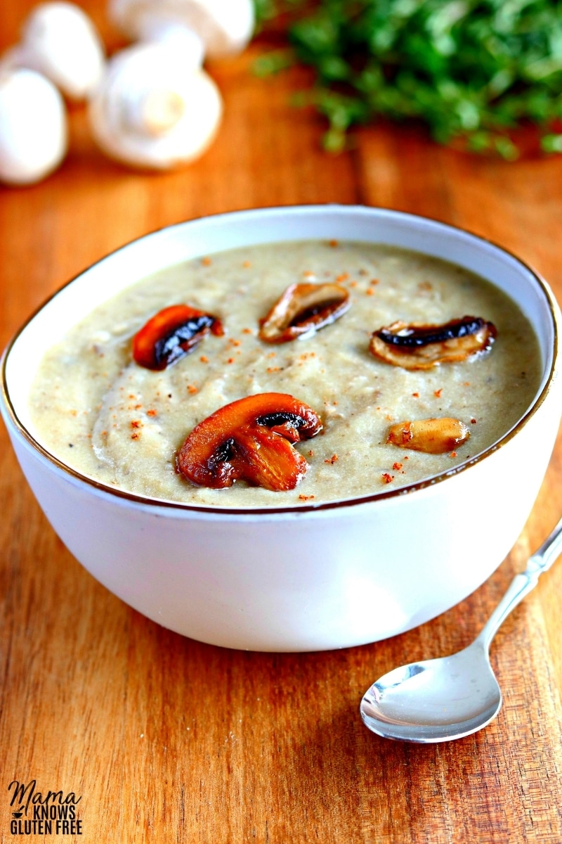 gluten-free cream of mushroom soup in a white bowl with and spoon and thyme and mushrooms in the background.