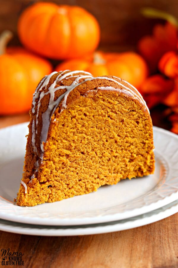 slice of gluten-free bundt cake on a white plate with pumpkins in the background