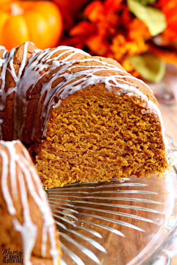 gluten-free pumpkin bundt cake sliced with pumpkin in the background