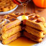 three gluten-free pumpkin waffels ona plate with syrup being poured on it