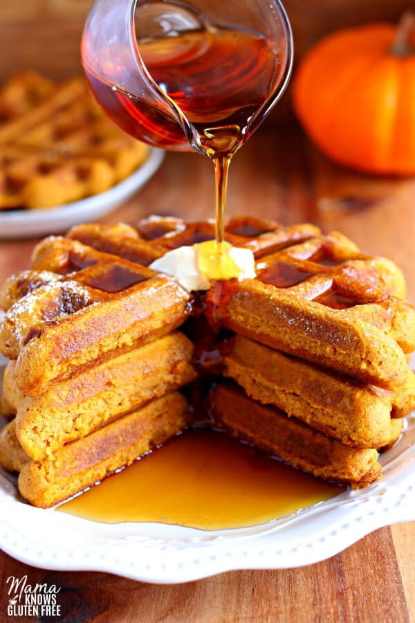 three gluten-free pumpkin waffles with butter and syrup being poured on it.