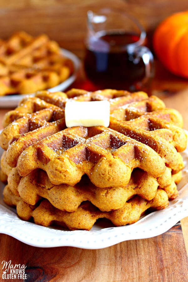 3 gluten-free pumpkin waffles with butter on a plate with syrup in the background.
