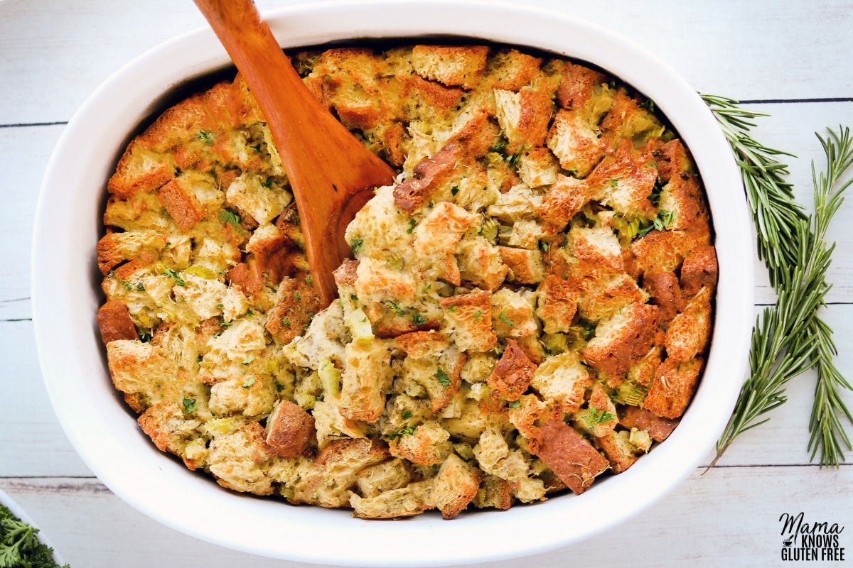 gluten-free stuffing in a round white baking dish with a wooden spoon