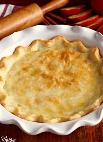 gluten-free baked pie crust with apples and a rolling pin in the background