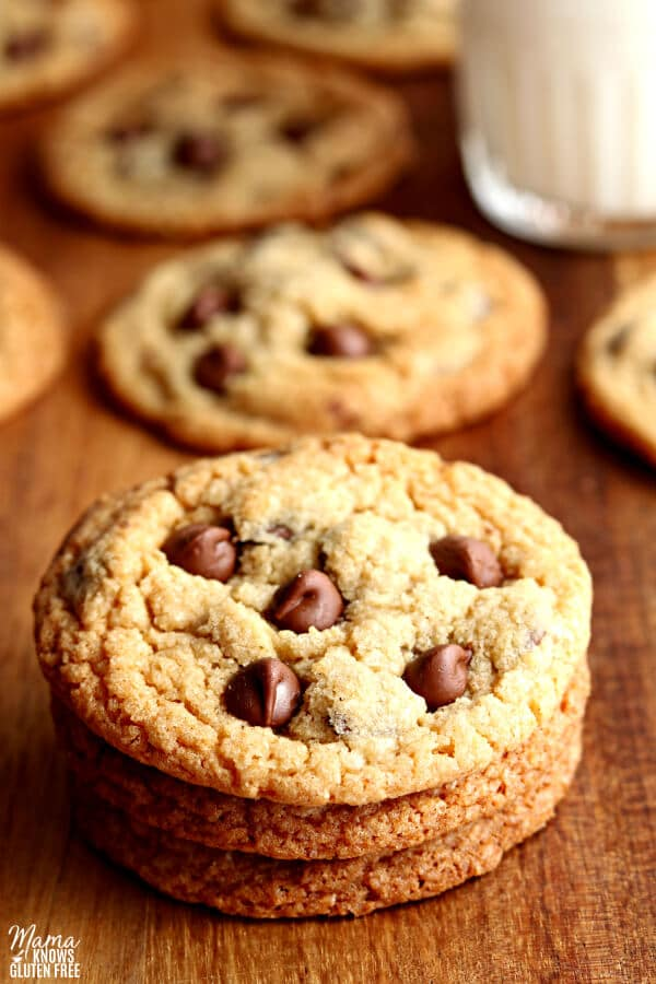 3 gluten-free chocolate chip cookies stacked on top of each other with cookies and milk in the background